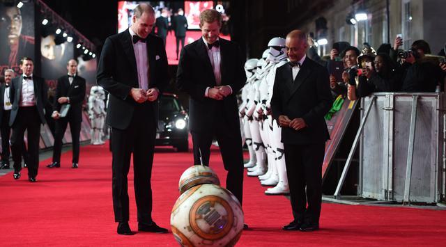 Pangeran William dan Pangeran Harry melihat robot droid BB-8 ketika berjalan di karpet merah premiere film The Star Wars: The Last Jedi yang digelar di The Royal Albert Hall, London, Inggris, Selasa (12/12). (Eddie Mulholland/Pool Photo via AP)