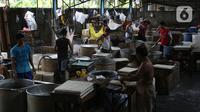 Pekerja memotong tahu yang baru dicetak di industri rumahan kawasan Jakarta, Selasa (17/12/2019). Pemerintah juga menaikkan plafon penyaluran KUR plafon secara signifikan 36% dari Rp 140 triliun menjadi Rp 190 triliun tahun 2020. (Liputan6.com/Angga Yuniar)