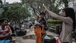 Seorang pria menggendong balita sambil memegang jersey Persija Jakarta saat menyaksikan pawai kemenangan Juara Piala Presiden di kawasan Bundaran HI, Minggu (18/2). Atribut-atribut bernuansa Persija berkibar selama konvoi. (Liputan6.com/Faizal Fanani)
