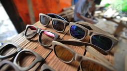 Sejumlah kacamata berbahan baku kayu di Gang  Madrasah, Pamulang, Tangerang Selatan, Senin (21/1). Dalam sehari, pengrajin mampu menyelesaikan dua buah kacamata yang dijual Rp 200 ribu hingga Rp 500 ribu per buah. (Merdeka.com/Arie Basuki)