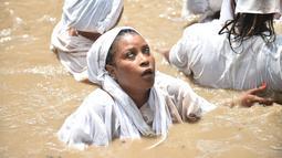 Seorang wanita pengikut Voodoo Haiti mandi di kolam suci selama upacara voodoo di Souvenance, Haiti (4/1). Voodoo dibawa ke Haiti oleh para budak dari Afrika Barat. (AFP/Hector Retamal)