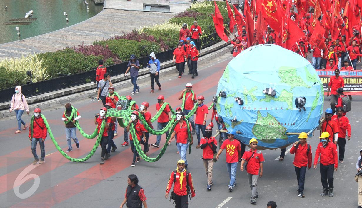 Massa buruh dari KASBI membawa gurita raksasa, bola dunia dan tikus pada peringatan May Day di Bundaran HI, Jakarta, Senin (1/5). Replika gurita itu dianggap simbol penghisap sumber daya alam yang ada di Indonesia. (Liputan6.com/Angga Yuniar)