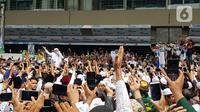 Rizieq Shihab menyapa massa yang menunggunya di Terminal 3 Kedatangan Bandara Soekarno-Hatta, Tangerang, Selasa (10/11/2020). Pimpinan FPI dan rombongan tiba di Tanah Air dengan menumpang pesawat Saudi Arabia Airlines SV816, rute Jeddah-Jakarta. (Liputan6.com/Herman Zakharia)