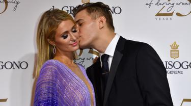 Model AS Chris Zylka mencium tunangannya Paris Hilton saat tiba menghadiri Pesta de Grisogono di sela-sela Festival Film Cannes ke-71 di Villa des Oliviers di Cap d'Antibes, Cannes, Prancis (15/5). (AFP Photo/Yann Coatsaliou)
