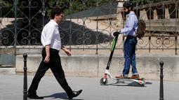 Seorang pria menggunakan skuter listrik saat beraktivitas di Paris, Prancis (9/7). Skuter listrik ini dibuat oleh perusahaan AS Lime yang merupakan penyewaan transportasi sepeda dan skuter di berbagai kota. (AFP Photo/Francois Guillot)