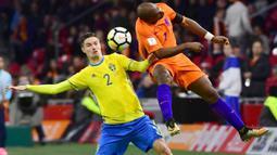 Duel pemain Belanda, Ryan Babel dan pemain Swedia, Mikael Lustig pada kualifikasi Piala Dunia 2018 grup A di Amsterdam Arena, Amsterdam (10/10/2017). Belanda menang 2-0. (AFP/Emmanuel Dunand)