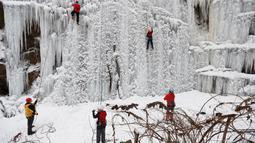 Orang-orang memanjat dinding es buatan di kota Liberec, Republik Ceko, Minggu (27/1). Meski buatan, tidak sembarang orang bisa menaklukkan tebing es tersebut. (AP Photo/Petr David Josek)