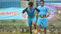 Asisten pelatih Arema FC, Kuncoro (belakang) saat ikut berlatih dengan tim karena minim jumlah pemain. (Bola.com/Iwan Setiawan)