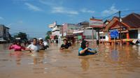 Sejumlah warga berjalan di genangan banjir yang merendam kota Bandung, Jawa Barat, Minggu (13/3). Kawasan Bandung Selatan kembali dilanda banjir akibat luapan Sungai Citarum dan membuat lebih dari 3000 jiwa mengungsi. (Timur Matahari/AFP)