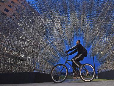Seorang pria mengendarai sepeda melewati instalasi seni seniman China Ai Weiwei yang berjudul 'Forever Cycles' di Rio de Janeiro, Brasil, Senin (19/8/2019). Instalasi ini terdiri lebih dari 1.000 sepeda stainless steel. (CARL DE SOUZA/AFP)