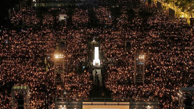 Puluhan ribu orang berkumpul sambil menyalakan lilin untuk memperingati Insiden Tiananmen di Taman Victoria Hong Kong (4/6). (AP/Vincent Yu)