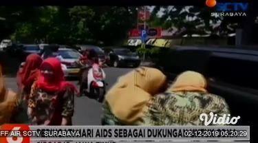 Puluhan dokter rumah sakit dan para medis di Kabupaten Sidoarjo membubuhkan cap lima jari dan bagikan bunga kepada pengendara yang melintas di Jalan Raden Fatah Sidoarjo. Aksi mereka untuk memperingati hari AIDS sedunia, 1 Desember.
