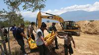 Petugas membawa jenazah korban gempa dan tsunami untuk dimakamkan massal di Palu, Sulawesi Tengah, Senin (1/10). Gempa dan tsunami yang melanda Palu serta Donggala telah menewaskan ratusan korban jiwa. (AP Photo/Tatan Syuflana)