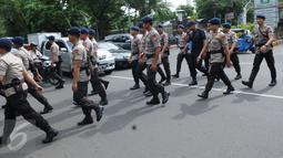 Sejumlah petugas kepolisian saat tiba di Gereja Katedral, Jakarta, Sabtu (24/12). Penjagaan oleh polisi dilakukan untuk menjaga kondusifitas agar acara Malam Misa Natal bisa berjalan lancar. (Liputan6.com/Helmi Afandi)