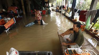 Seorang pria duduk di ranjang bambu saat banjir menyusul hujan di pinggiran Phnom Penh, Kamboja (14 /10/2020). Pejabat bencana Kamboja mengatakan Rabu bahwa lebih dari 10.000 orang telah dievakuasi ke tempat aman setelah badai tropis melanda yang menyebabkan banjir bandang.  (AP Photo/Heng Sinith)