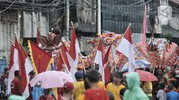 Atraksi liong saat perayaan Cap Go Meh Tahun Baru Imlek 2571 di Jatinegara, Jakarta, Minggu (9/2/2020). Meski hujan, perayaan Cap Go Meh berlangsung meriah dengan atraksi barongsai dan liong serta arakan dewa-dewa (rupang), mengelilingi kawasan Jatinegara. (merdeka.com/Iqbal S Nugroho)