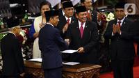 Joko Widodo atau Jokowi (kedua kiri) menyerahkan berkas kepada Ketua MPR Bambang Soesatyo saat dilantik menjadi Presiden RI periode 2019-2024 di Gedung Nusantara, Jakarta, Minggu (20/10/2019). Jokowi dan Ma'ruf Amin resmi menjadi Presiden dan Wakil Presiden RI. (Liputan6.com/JohanTallo)