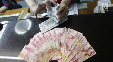 Teller menukarkan mata uang dolar ke rupiah di Jakarta, Jumat (2/2). Deputi Gubernur Senior BI Mirza Adityaswara mengatakan, posisi nilai tukar rupiah terhadap dolar Amerika Serikat yang berada di level Rp13.700 hingga Rp13.800.(Liputan6.com/Angga Yuniar)