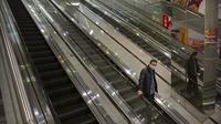 Seorang pria mengenakan masker turun menggunkan eskalator di pusat perbelanjaan yang sepi pengunjung di Beijing (28/1/2020).  Mewabahnya virus corona membuat pusat perbelanjaan di Beijing, China, sepi pengunjung. (AP Photo/Mark Schiefelbein)