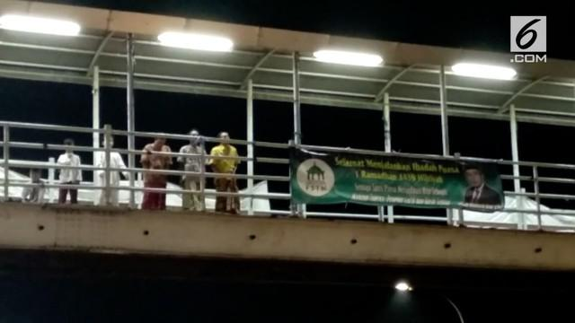 Beberapa warga Cipinang terpaksa Salat Tarawih di jembatan penyeberangan karena kondisi masjid yang penuh.