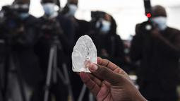 Seorang anggota kabinet Botswana memegang berlian permata di Gaborone, ibu kota Botswana, Rabu (16/6/2021). Batu itu - seberat 1.098 karat - diperlihatkan kepada Presiden Mokgweetsi Masisi, dua minggu setelah perusahaan berlian, Debswana, menggalinya. (Monirul Bhuiyan/AFP)