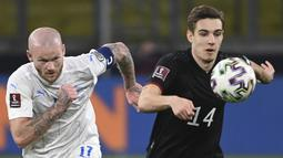 Gelandang Islandia Aron Gunnarsson (kiri) dan gelandang Jerman Florian Neuhaus bersaing memperebutkan bola pada pertandingan kualifikasi Piala Dunia 2022 Zona Eropa Grup J di Duisburg, Jumat (26/3/2021) dinihari WIB. Jerman berhasil melumat Islandia dengan skor 3-0. (Ina Fassbender/AFP)