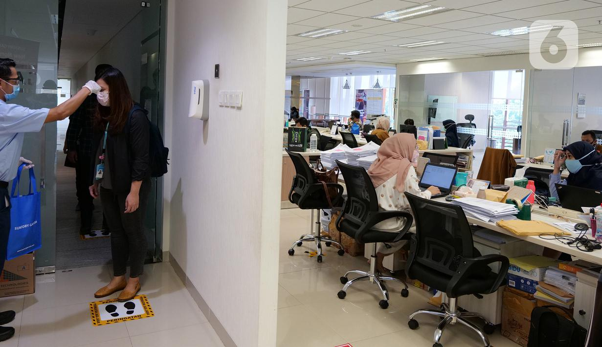 Petugas mengecek suhu tubuh karyawan sebelum memasuki ruang kerja di Suntory Garuda, Jakarta, Senin (8/8/2020). Perusahaan tersebut menerapkan protokol kesehatan saat hari pertama kerja di masa PSBB transisi yang diterapkan oleh Pemprov DKI Jakarta. (Liputan6.com/Herman Zakharia)