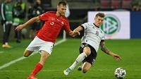 Gelandang Jerman, Toni Kroos, berebut bola dengan bek Swiss, Silvan Widmer, pada laga lanjutan UEFA Nations League 2020/2021 di RheinEnergie Stadion, Rabu (14/10/2020). Jerman bermain imbang 3-3 atas Swiss. (AFP/Ina Fassbender)