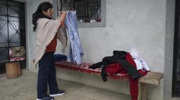 Calon ibu negara Peru, Lilia Paredes (48) melipat baju suaminya saat mengemasi barang-barang keluarga, di halaman rumahnya di Chugur, pada 22 Juli 2021. Suaminya, Pedro Castillo yang merupakan mantan guru dan pemimpin serikat pekerja memenangkan pemilihan presiden Peru. (AP/Franklin Briceno)