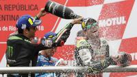 Juara MotoGP Argentina, Cal Crutchlow dari tim LCR Honda menyemprotkan sampanye pada pembalap Yamaha Tech 3, Johann Zarco di atas podium Sirkuit Termas de Rio Hondo, Minggu (8/4). Crutchlow berhasil menjadi juara MotoGP Argentina. (AP/Natacha Pisarenko)