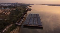 Tongkang menunggu untuk diangkut di tengah kekeringan berkelanjutan yang mempengaruhi ketinggian air sungai Paraguay di pantai tepi San Miguel, Paraguay, Senin (20/9/2021).  (AP Photo/Jorge Saenz)