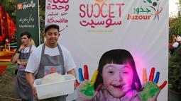 "Seorang anak down syndrome Abdel Rahman bekerja di kedai kopi Sucet  selama festival ""Sham gather us"" di Damascus (11/7). Enam belas anak laki-laki dan perempuan down syndrome bekerja di Cafe Sucet melayani pelanggan. (AFP Photo/Louai Beshara)"