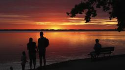 """Orang-orang menikmati matahari terbenam di danau Chiemsee di Chieming, Jerman, Selasa, (25/8/2020).  Danau yang terletak di dekat kota Rosenheim ini sering diberi julukan """"Laut Bayern'. (AP Photo / Matthias Schrader)"""