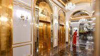 Seorang pegawai berdiri di dekat lift hotel Dolce Hanoi Golden Lake yang baru saja diresmikan di Hanoi, Vietnam pada Kamis (2/7/2020). Hotel tersebut merupakan hotel berlapiskan emas 24 karat pertama di dunia. (Manan VATSYAYANA / AFP)
