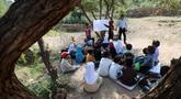 Anak-anak menghadiri kelas terbuka di bawah pohon dekat sekolah mereka yang belum selesai pada tahun ajaran baru di negara yang dilanda perang di desa al-Kashar Yaman barat daya di distrik Mashraa dan Hadnan di provinsi Taez (16/9/2019). (AFP Photo/Ahmad Al-Basha)