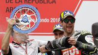 Pembalap LCR Honda, Cal Crutchlow menyemprotkan sampanye pada salah satu krunya saat merayakan kemenangannya pada balapan MotoGP Argentina di atas podium Sirkuit Termas de Rio Hondo, Minggu (8/4). (AP/Natacha Pisarenko)