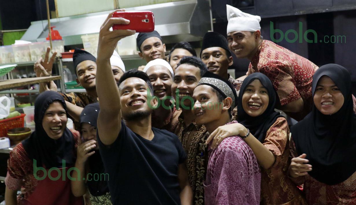 Andik Vermansah berfoto bersama karyawan rumah makan Wong Solo di Selangor, Malaysia, Rabu (27/01/2016). (Bola.com/Nicklas Hanoatubun)