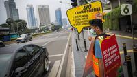 Relawan yang tergabung dalam Gerakan Mahasiswa Cegah Covid-19 membawa poster 'Ayo Lawan Corona' saat kampanye di Pelican Cross kawasan Thamrin, Jakarta, Senin (23/3/2020). (Liputan6.com/Faizal Fanani)
