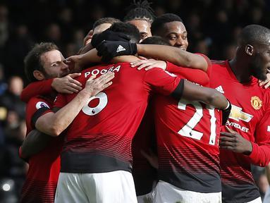 Para pemain Manchester United merayakan gol yang dicetak Paul Pogba ke gawang Fulham pada laga Premier League di Stadion Craven Cottage, London, Sabtu (9/2). Fulham kalah 0-3 dari MU. (AFP/Ian Kington)