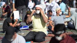 Jemaah mengenakan masker untuk menghindari penyebaran COVID-19 saat menunggu di distrik bersejarah Sultanahmet, dekat Hagia Sophia, Istanbul, Turki, Jumat (24/7/2020). Umat muslim melaksanakan salat Jumat pertama di Hagia Sophia dalam 86 tahun terakhir. (AP Photo/Yasin Akgul)