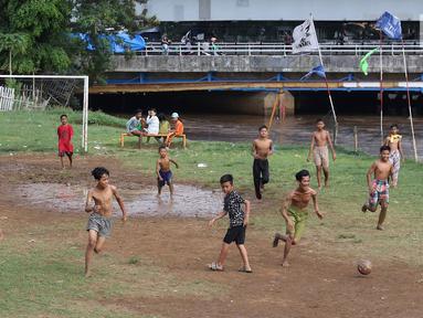 Anak-anak bermain sepak bola di bantaran Kanal Banjir Barat, Jakarta, Jumat (5/4). Tidak adanya lapangan menjadikan lokasi tersebut sebagai tempat bermain mereka, meskipun dalam kondisi seadanya. (Liputan6.com/Immanuel Antonius)