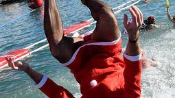 Peserta berkostum Sinterklas melompat ke dalam air pada kompetisi renang 'Copa Nadal' di Port Vell, Barcelona, Rabu (25/12/2019). Lebih dari 300 peserta menempuh jarak sejauh 200 meter pada tradisi lama yang digelar  saat hari Natal tersebut. (Josep LAGO / AFP)