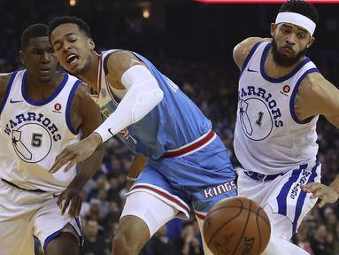 Ekspresi pemain Sacramento Kings, Skal Labissiere (tengah) saat berebut bola dengan dua pemain Warriors  pada laga NBA basketball game di Golden 1 Center, Oakland, California, (16/3/2018). King menang 98-93. (AP/Ben Margot)