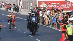 Pelari maraton Jepang, Hiroto Inoue bersaing dengan Elhassan Elabbassi dari Bahrain saat memasuki garis finis lomba Asian Games 2018 di jalan Sudirman, Jakarta, Sabtu (25/8). Hiroto menjadi pemenang lari maraton 42 kilometer. (Merdeka.com/Imam Buhori)
