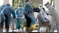 Staf kementerian kesehatan mengumpulkan sampel untuk pengujian virus corona dari seorang penduduk di daerah perkotaan di Bandar Utama, pinggiran Kuala Lumpur, Malaysia pada hari Kamis, 22 Oktober. (Vincent Thian / AP)