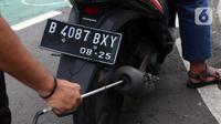 Petugas memeriksa emisi motor di Jakarta Barat, Rabu (13/1/2021). Dinas Lingkungan Hidup DKI Jakarta mengumumkan kendaraan yang tidak mengikuti uji emisi atau tidak lulus uji emisi gas buang akan dikenakan disinsentif tarif parkir yang tinggi dan tilang. (Liputan6.com/Angga Yuniar)