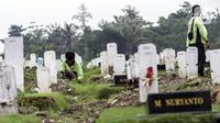 Sejumlah petugas membersihkan makam di Srengseng Sawah, Jakarta, Selasa (15/6/2021). Gubernur DKI Jakarta Anies Baswedan menjelaskan alasan angka kematian akibat COVID-19 di Jakarta relatif stabil dan terhitung sangat rendah. (Liputan6.com/Johan Tallo)