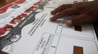 Petugas KPU menunjukan surat suara untuk pemilih tunanetra dengan huruf braile di Kantor KPU, Kebon Jeruk, Jakarta, Kamis (2/2). (Liputan6.com/Yoppy Renato)