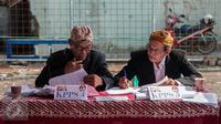 Petugas KPPS mengenakan pakaian adat dan belangkon melihat lembaran data pemilih di TPS 14 Cipinang Besar Selatan, Jakarta, Rabu (19/4). Petugas KPPS menggunakan pakaian adat tersebut agar warga tertarik untuk mencoblos. (Liputan6.com/Gempur M. Surya)