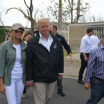 Presiden AS Donald Trump dan ibu negara Melania Trump berkeliling ke permukiman yang terdampak Badai Maria di Guaynabo, Puerto Rico, Selasa (3/10). Akan tetapi, dalam kunjungan itu Melania terlihat menggunakan celana jins berwarna putih. (MANDEL NGAN/AFP)